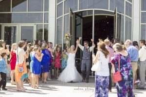 bride and groom celebrating amid bubble exit for post on perfect timeline for wedding photos