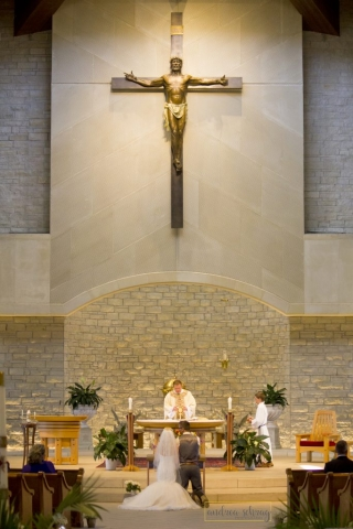 bride and groom kneeling at front of sanctuary