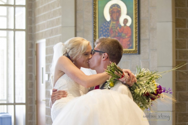 bride and groom kissing while groom holds bride