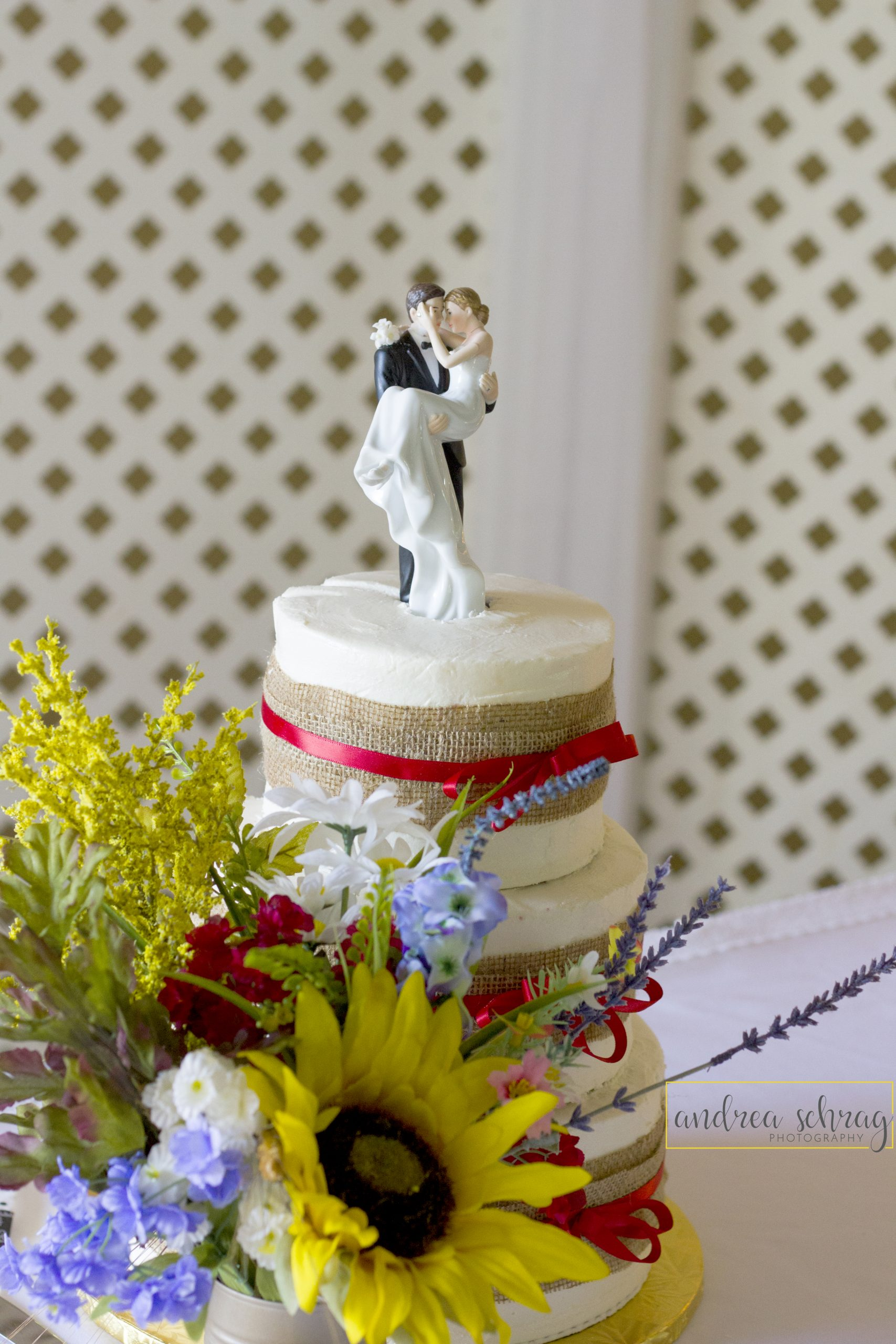 white wedding cake with burlap and red ribbon