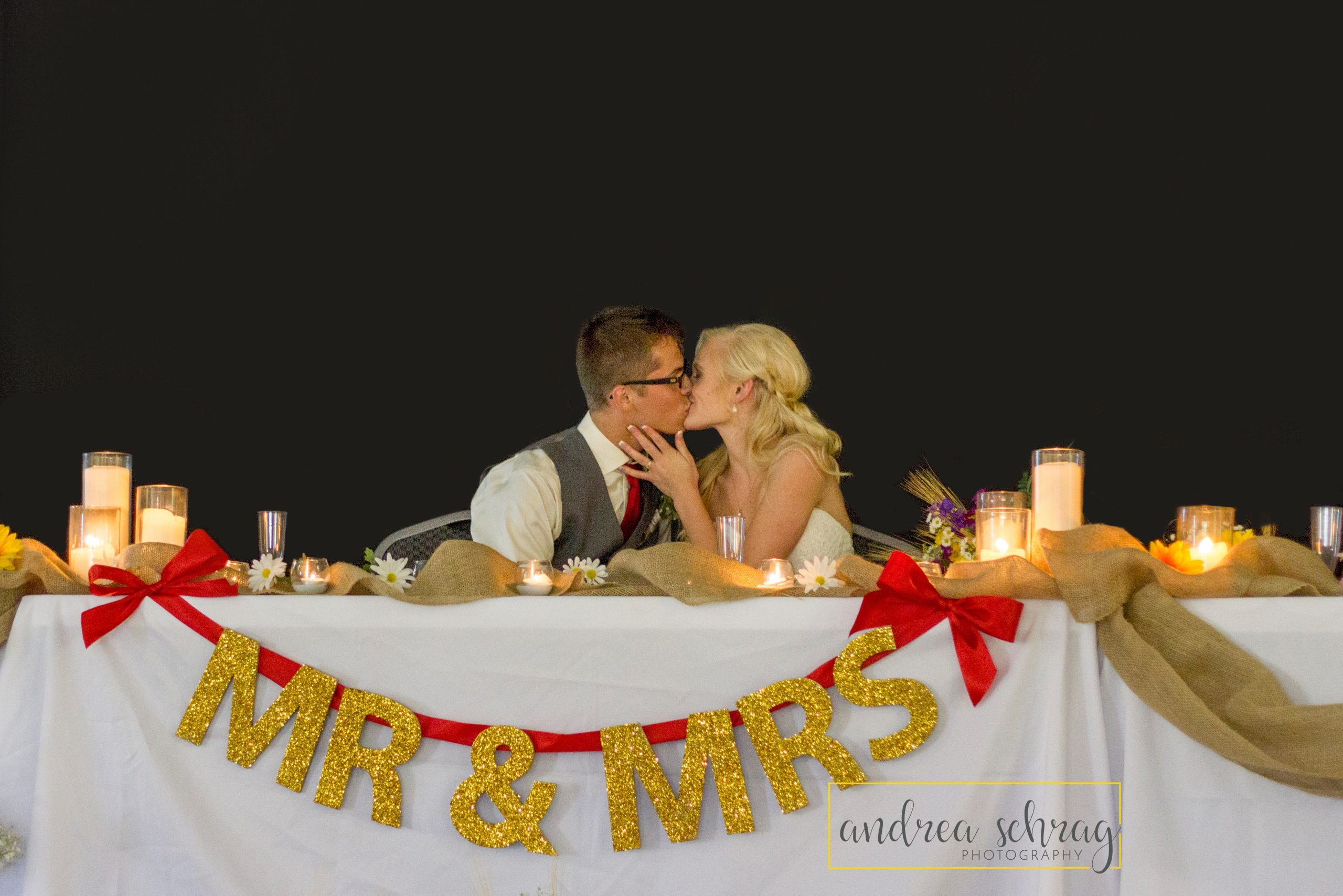 new bride and groom kissing at reception table